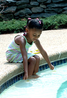 100169 Little Girl Playing At Edge Of Swimming Pool