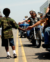 100068 Motorcyclist Extends His Hand To Youth