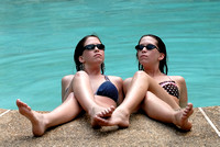 101576 Twin Sisters In Bathing Suits Sitting Partially In Pool